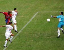 Mario el Coyote Acevedo, delantero de Municipal, cabecea frente a Rigoberto Gómez, para conseguir el segundo gol de los rojos en el triunfo por 4-1 en el clásico 216 (Foto Prensa Libre: Hemeroteca PL)
