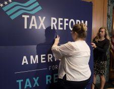 """Empleados colocan un cartel en el que se lee """"Tax Reform"""" (Reforma fiscal) durante un acto para promover el plan republicano de reforma fiscal, en el Capitolio. (Foto Prensa Libre: EFE)"""
