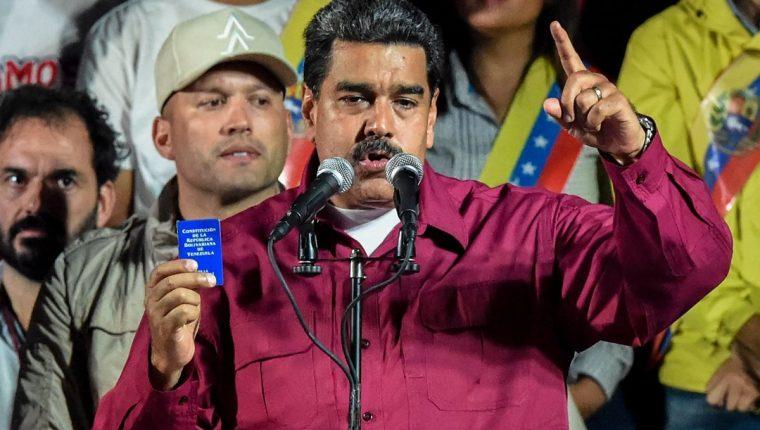 Nicolás Maduro sostiene la Constitución política después de que el Consejo Nacional Electoral (CNE) anunció los resultados de la votación.(Foto Prensa Libre:AFP).