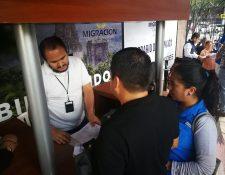 Personal de Migración entrega números a dos personas que llegaron a realizar su trámite. (Foto Prensa Libre: Estuardo Paredes)