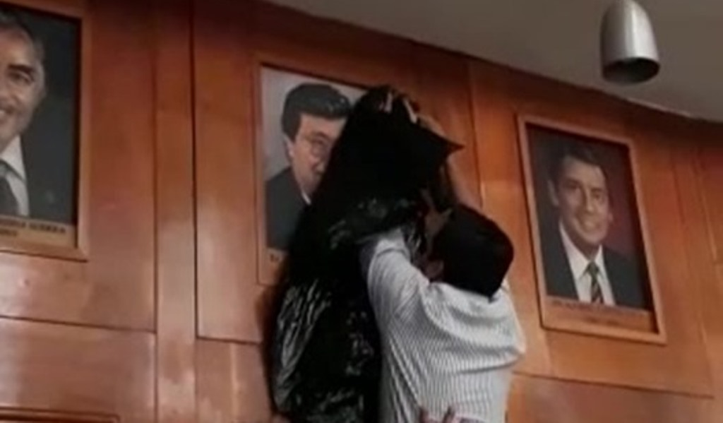 Momento en que integrantes del Consejo Superior Universitario tapan con una bolsa negra la fotografía del exrector Jafeth Cabrera, quien fue declarado no grato junto al presidente Jimmy Cabrera. (Foto Prensa Libre: Cortesía)