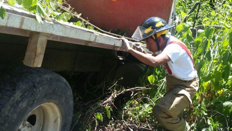 Bombero inspecciona el área donde se accidentó el camión en la comunidad Parraxtut. (Foto Prensa Libre: Héctor Cordero).