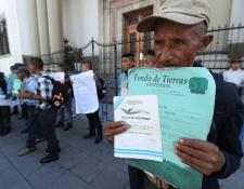Campesinos muestran títulos de propiedad de los terrenos que, aseguran, les arrebataron para la construcción de la represa de Chixoy. (Foto Prensa Libre: Esbin García)