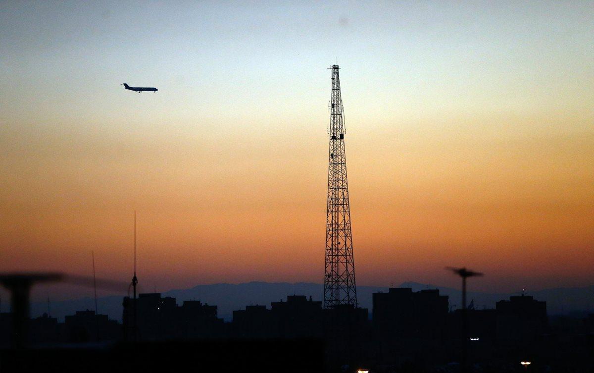Un avión de pasajeros iraní pasa junto a una colorida puesta de sol que ilumina el cielo en la capital iraní Teherán, Irán. (Foto Prensa Libre:EFE).