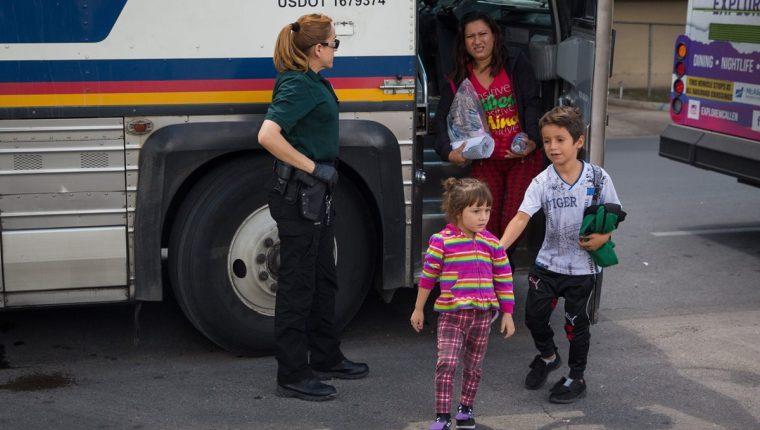 Una agente de migración observa a una familia en McAllen, Texas, después de haber sido detenidos en la frontera. (Foto Prensa Libre: AFP)
