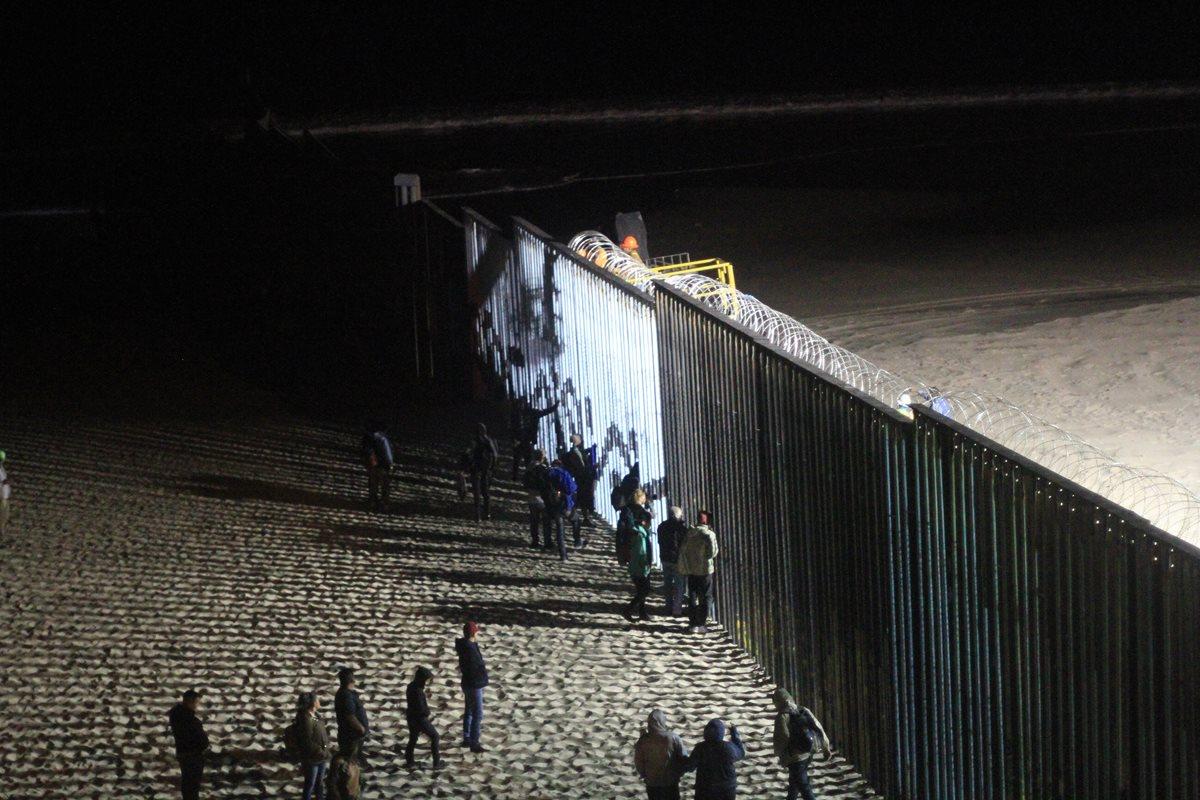 Agentes del ejército norteamericano vigilan este miércoles a los migrantes de la primera caravana que salió desde Honduras y recorrió el territorio mexicano en la valla fronteriza de Tijuana, México. (Foto Prensa Libre: EFE)