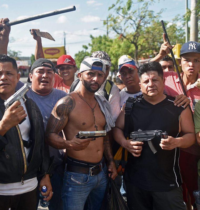 """Un grupo de comerciantes del supermercado """"Mercado Mayoreo"""" se armaron para proteger sus mercancías. (Foto Prensa Libre: AFP)"""