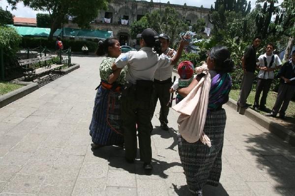 La imagen, captada en  julio del 2010, muestra el momento en que  policías  de Turismo arrebatan collares típicos a vendedora.
