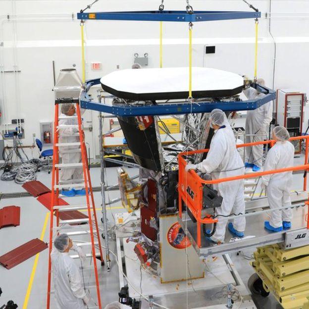 Los ingenieros del Laboratorio de Física Aplicada de la Universidad John Hopkins colocan el escudo protector sobre la sonda. El escudo está pintado de blanco para reflejar la luz del Sol. (NASA/John Hopkins APL)