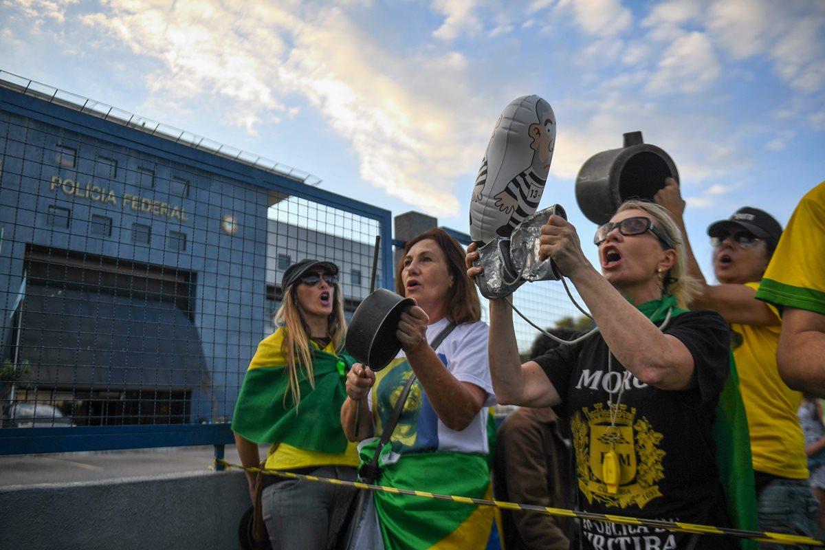 Opositores del ex presidente brasileño (2003-2011) Luiz Inácio Lula da Silva gritan consignas mientras esperan frente a la sede de la Policía Federal, donde debe comenzar su sentencia de 12 años de prisión, en Curitiba, estado de Paraná, Brasil.