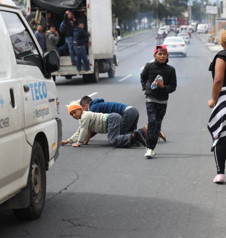 Un vehículo frena a pocos metros de donde un grupo de hondureños recogían monedas que un automovilista les lanzó, para apoyarlos en su travesía hacia EE. UU. (Foto Prensa Libre: Óscar Rivas)