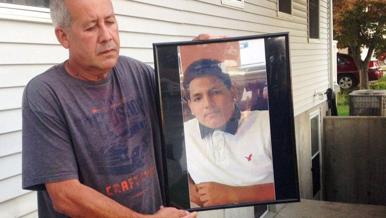 Abraham Chaparro sostiene la fotografía de su hijastro, Miguel García Morán, quien habría sido asesinado por integrantes de pandillas centroamericanas. (Foto Prensa Libre: AP).