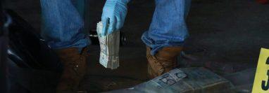 Un fiscal del MP cuanta parte de los dólares incautados en Cocales, Patulul, Suchitepéquez. (Foto Prensa Libre: Cristian Soto)
