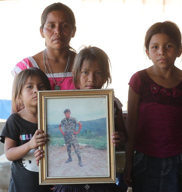 Las hijas de Nohemí sostienen la fotografía con la que recuerdan a su padre asesinado en 2012 por tropas beliceñas. (Foto Prensa Libre: Érick Ávila)