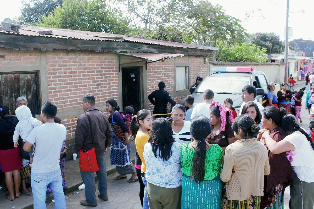 Familiares y vecinos de Rubén Inay, quien fue hallado muerto en su vivienda, en Chimaltenango, observan mientras las autoridades realizan las diligencias respectivas en la escena. (Foto Prensa Libre: Víctor Chamalé)