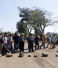 Pobladores de El Carmen bloquean el paso de camiones cañeros en la entrada de la comunidad. (Foto Prensa Libre: Rolando Miranda)