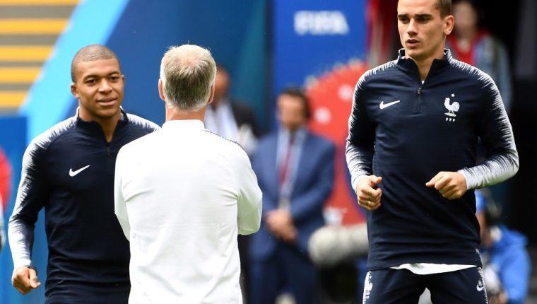Kylian Mbappé y Antoine Griezmann conversan con el director técnico de Francia Didier Deschamps. (Foto Prensa Libre: AFP)