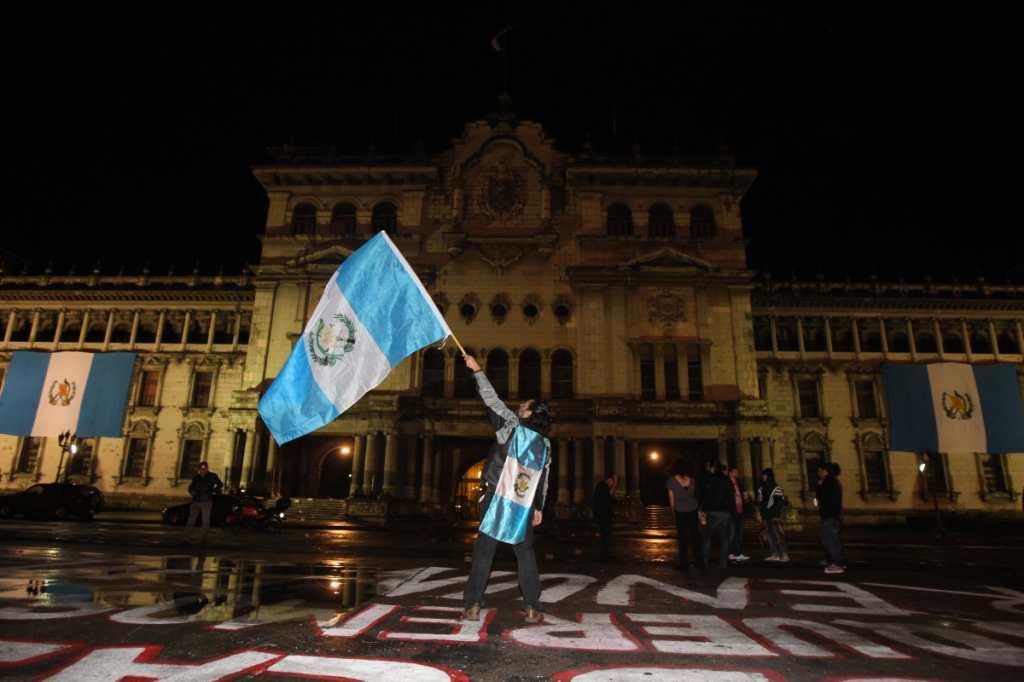 El cineasta Medel Samayoa ondea una bandera frente al Palacio Nacional.