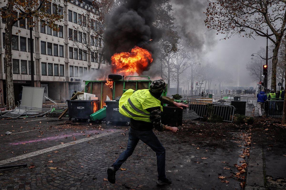 """Un manifestante de los autodenominados """"chalecos amarillos"""" se enfrentó a los agentes junto a una barricada en llamas durante los disturbios. (Foto Prensa Libre: EFE)"""