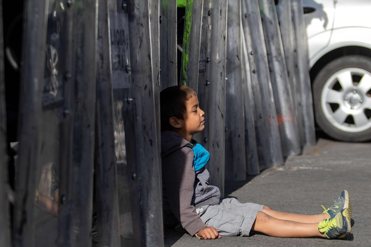 Un niño migrante centroamericano se sienta frente al cerco policial de antimotines que también México colocó. (Foto Prensa Libre: AFP)