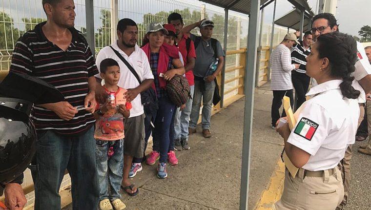 Personal del Instituto Nacional de Migración mexicano atiende a uno de los primeros grupos de nicaragüenses que llegaron a la frontera, después de un acuerdo para gestionar asilo. (Foto Prensa Libre: EFE)