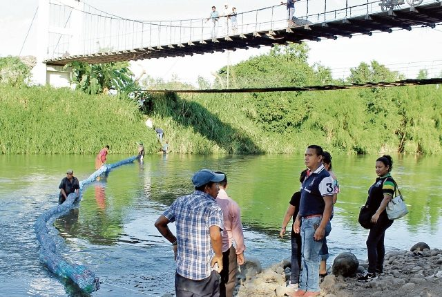 Personal del Ministerio de Ambiente instala la barrera que retendrá desechos plásticos. (Foto Prensa Libre: Oswaldo Cardona)