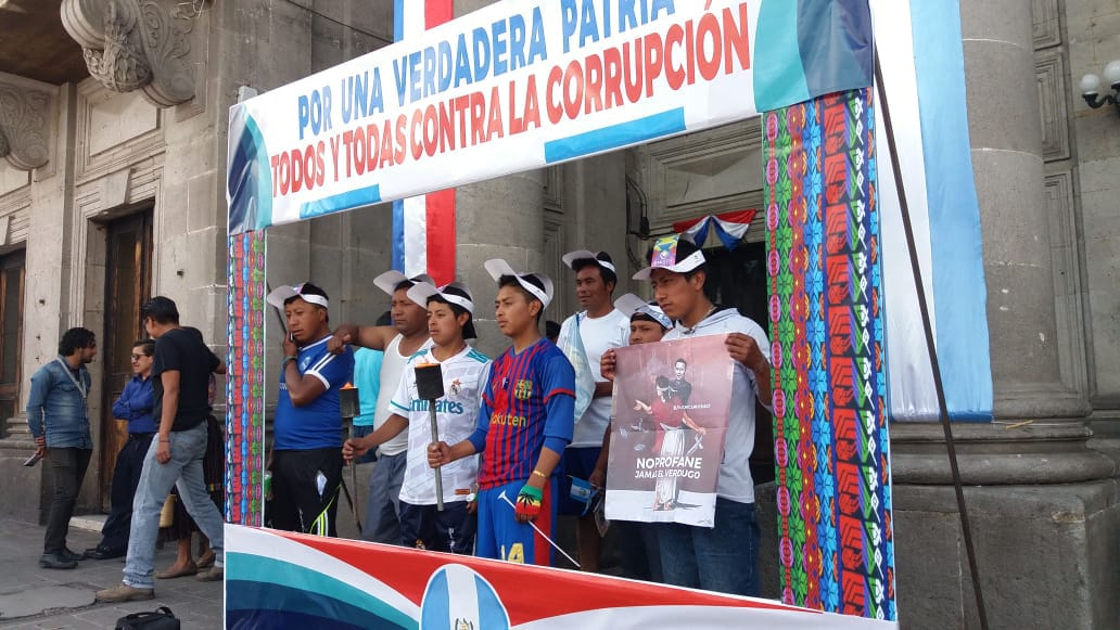 Integrantes del Colectivo Ciudadano colocaron este viernes un cartel en el parque central para que quienes participan en las actividades de Xelafer. (Foto Prensa Libre: Mynor Toc)