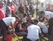 Socorristas atienden a las cinco personas que viajaban en una motocicleta y fueron arrollados.(Foto Prensa Libre: Jorge Tizol)