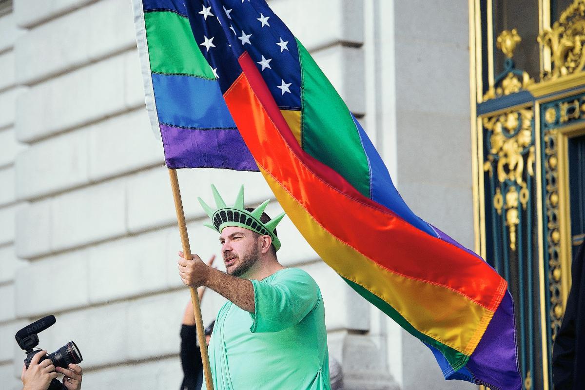 Un estadounidense porta una bandera del arco iris celebra la la decisión de la Corte Suprema de Estados Unidos. (Foto Prensa Libre:AP).