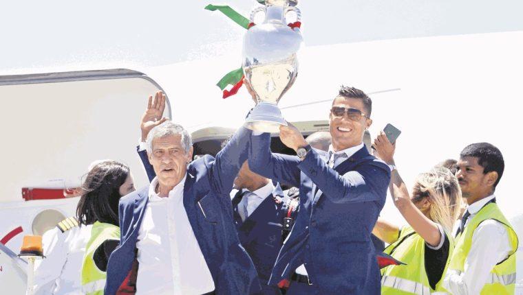 El técnico Fernando Santos junto a Cristiano Ronaldo cuando regresaron a Portugal, con el título de campeones de la Eurocopa. (Foto Prensa Libre: AFP)
