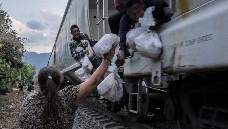 """Una mujer de Las Patronas da alimentos a los migrantes que viajan en """"la Bestia"""". (Foto: Las Patronas)"""