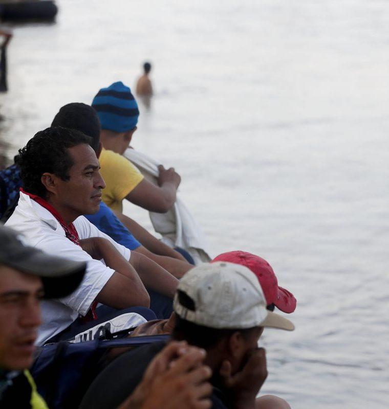 Migrantes hondureños observan desde orilla del río Suchiate a integrantes de Marina mexicana. (Foto Prensa Libre: EFE)