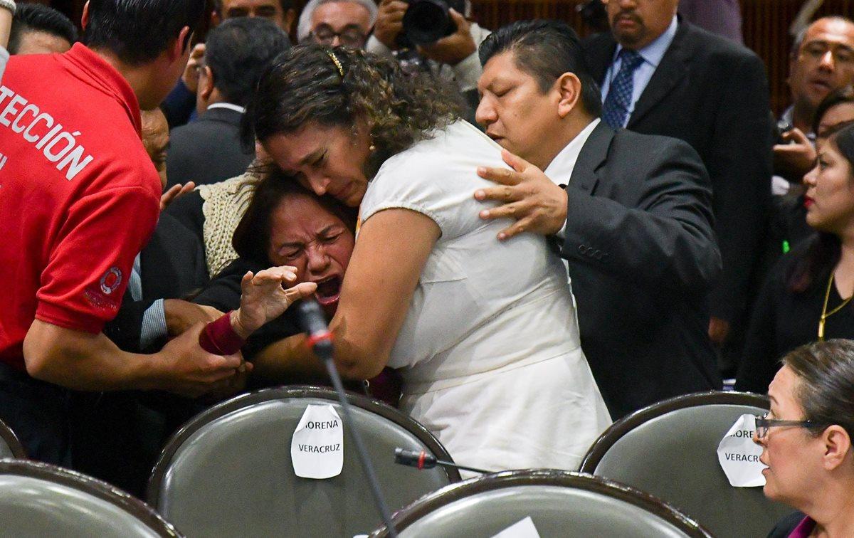 Legisladores reconfortan a la diputada Carmen Medel Palma, luego de que recibiera la noticia de que su hija había sido asesinada. (Foto Prensa Libre: EFE)