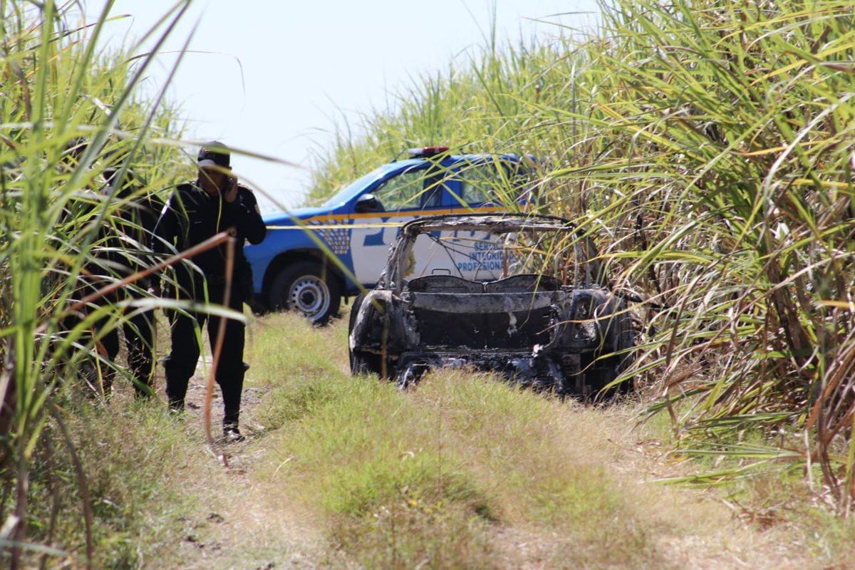 La Policía Nacional Civil inspecciona el lugar donde hallaron un automóvil carbonizado, en ruta a Puerto Quetzal, Escuintla. (Foto Prensa Libre: Redacción)