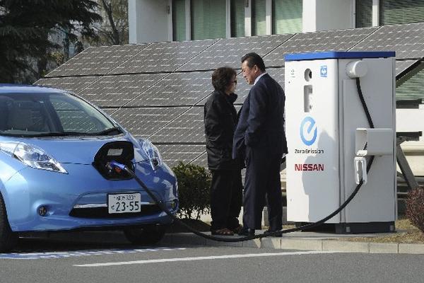 """Un hombre recarga el carro eléctrico del modelo """"Leaf"""" de Nissan en la fábrica de la compañía en Oppama (Japón). (Foto Prensa Libre: EFE)"""