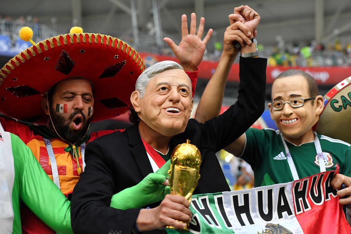 Un fanático de México porta una máscara que representa a Andrés Manuel López Obrador, aplaude con otros simpatizantes antes del partido de futbol entre Brasil y México. (AFP).