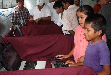 Niños y adultos de la comunidad Ribacó, Baja Verapaz, prueban  el  internet satelital, para el  cual se usa energía solar.