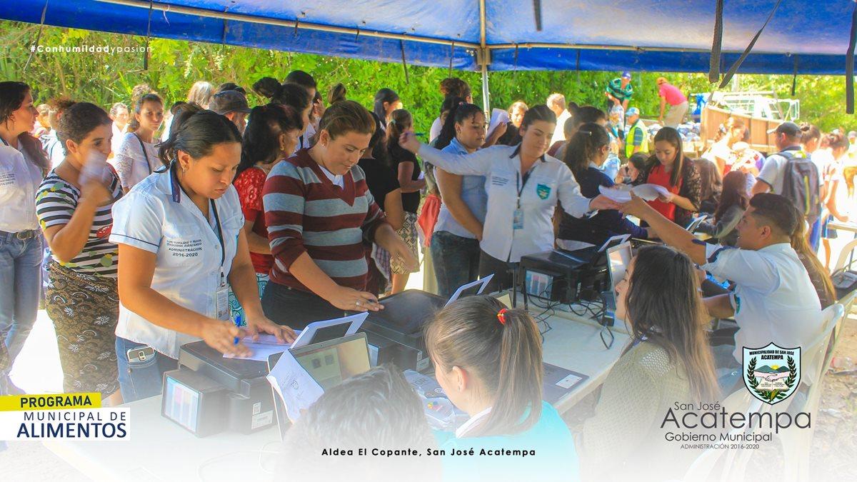 En una jornada de entrega de bolsas de víveres en San José Acatempa, Jutiapa, registran a los vecinos que reciben los alimentos. (Foto Prensa Libre)