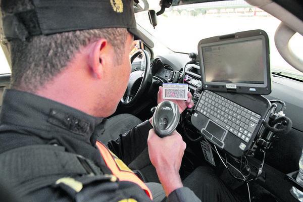 Un agente de la PNC verifica la situación legal de un conductor, mediante el escaneo de   una licencia de conducir. (Foto Prensa Libre: Álvaro Interiano)