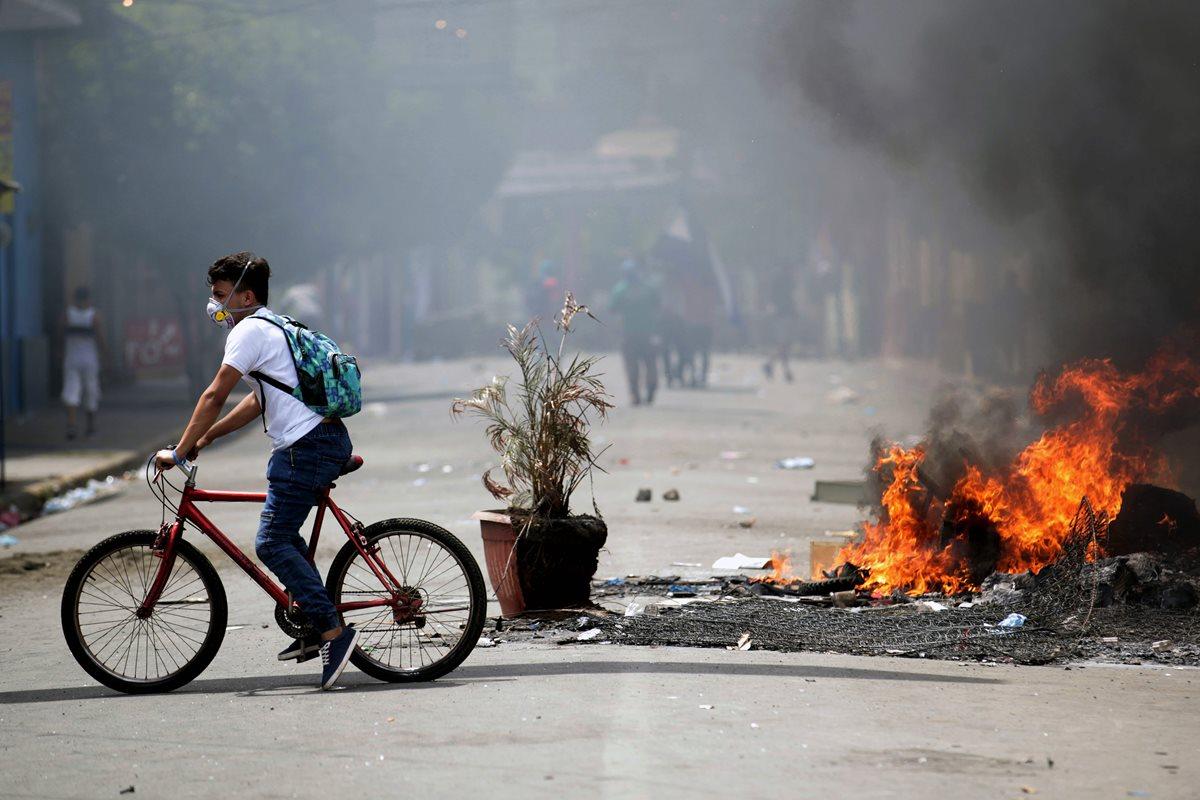 Un manifestante pasa durante las protestas nacionales que exigen justicia, democracia y la salida de Ortega, en Masaya, Nicaragua. (Foto Prensa Libre:AFP).