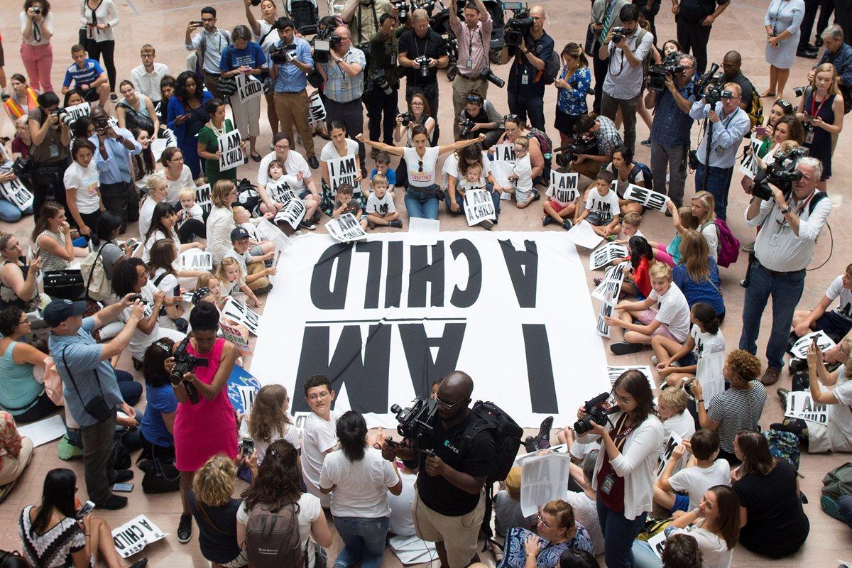 Niños y activistas participan en una protesta contra las políticas de separar a familias inmigrantes, en Washington. (Foto Prensa Libre: EFE)