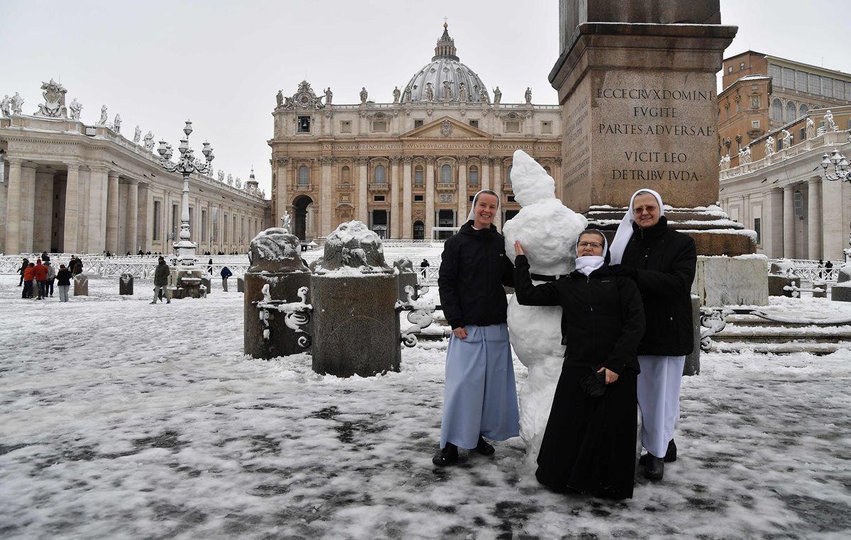 Monjas juegan con la nieve en la Plaza de San Pedro en el Vaticano. (Foto Prensa Libre: AFP)