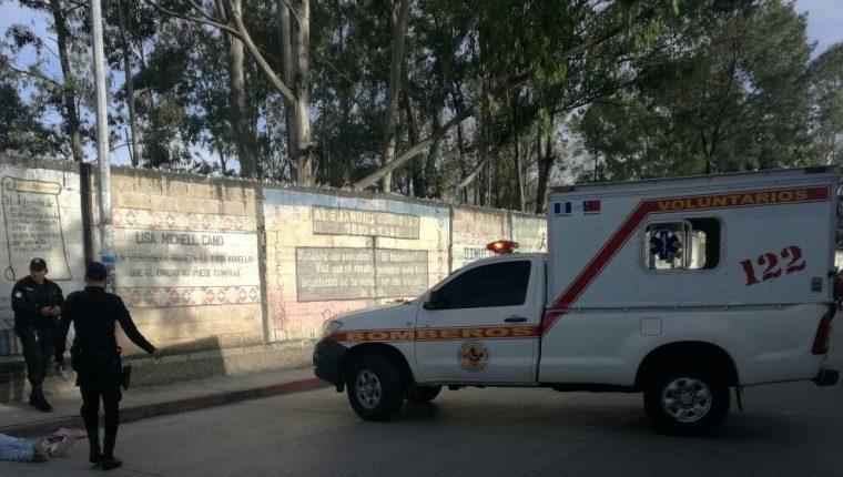 Agentes de la PNC resguardan el cadáver de un hombre que murió a balazos en la zona 1 de la cabecera de Huehuetenango. (Foto Prensa Libre: Mike Castillo)
