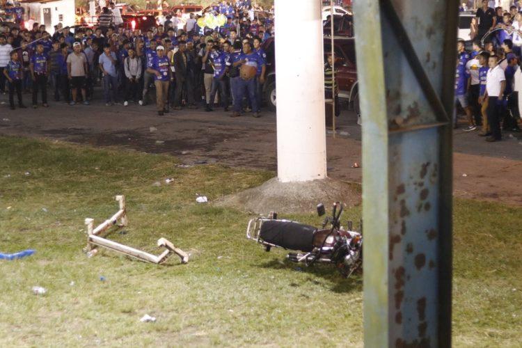 Varios aficionados observan una motocicleta que quedó tirada después de los disturbios.