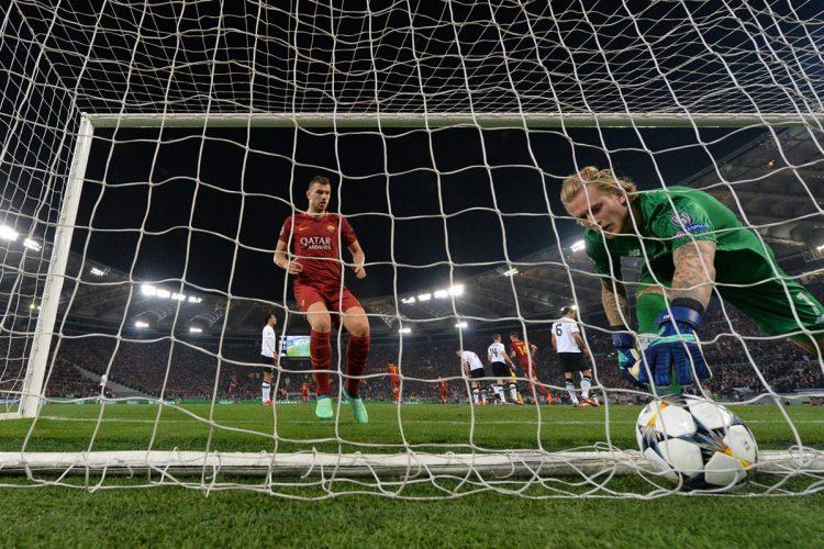 Edin Dzeko intenta sacar la pelota para apurar el reinicio del partido frente al portero Loris Kariu.