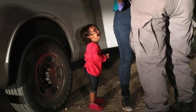 La fotografía que se ha vuelto viral y que muestra a una niña mientras llora en lo que la Policía registra a su madre. (Foto Prensa Libre AFP)