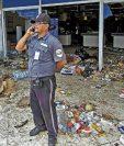 Un guardia de seguridad habla por teléfono tras el saqueo de un local comercial en Nicaragua producto de la ola de protestas contra el presidente Daniel Ortega por cambios en la seguridad social.