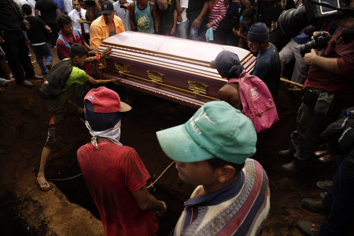 Varios nicaragüenses ayudan a sostener el féretro de una de las víctimas de la familia que murió ayer calcinada de Managua, Nicaragua. (Foto Prensa Libre:EFE).