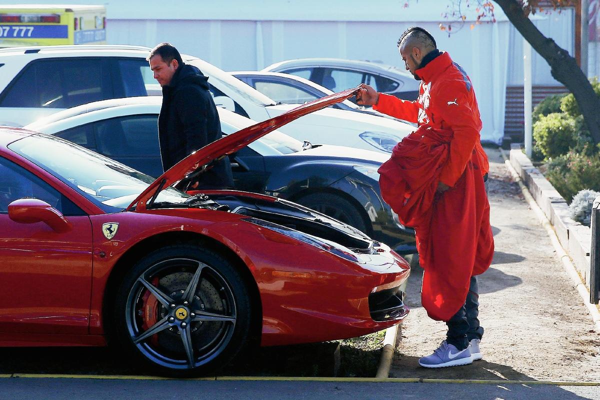 Arturo Vidal revisa su auto Ferrari ayer a la legada al entrenamiento matutino del equipo en el complejo deportivo Juan Pinto Durán. (Foto Prensa Libre: EFE)