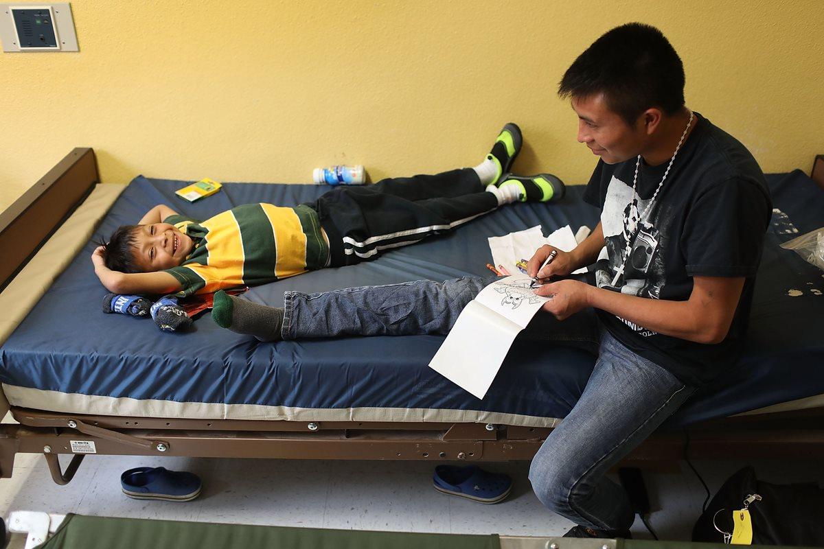 Un inmigrante guatemalteco identificado como Manuel junto a su hijo Agusto, 9 años en una casa facilitada para la reunificación en El Paso, Texas. (AFP)